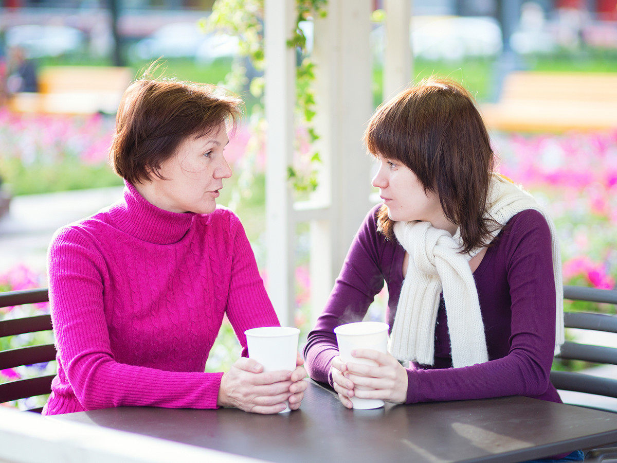Daughter has serious conversation with mother outdoors