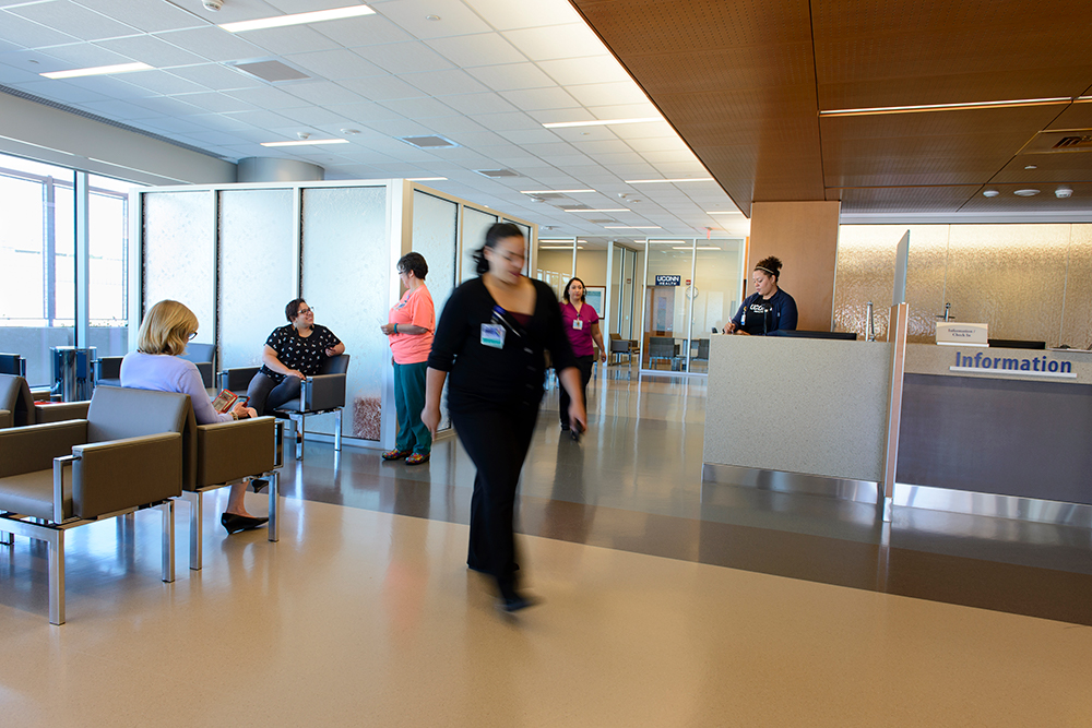 A patient and staff are seen inside the Emergency Department waiting area. A children's play area is inside opaque glass walls.