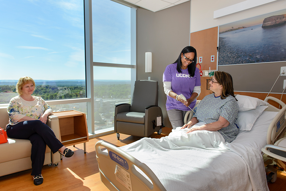 A UConn Health nurse shows a patient how to adjust her bed in a room on the sixth floor of the UConn Health new tower. It's open and spacious and large windows