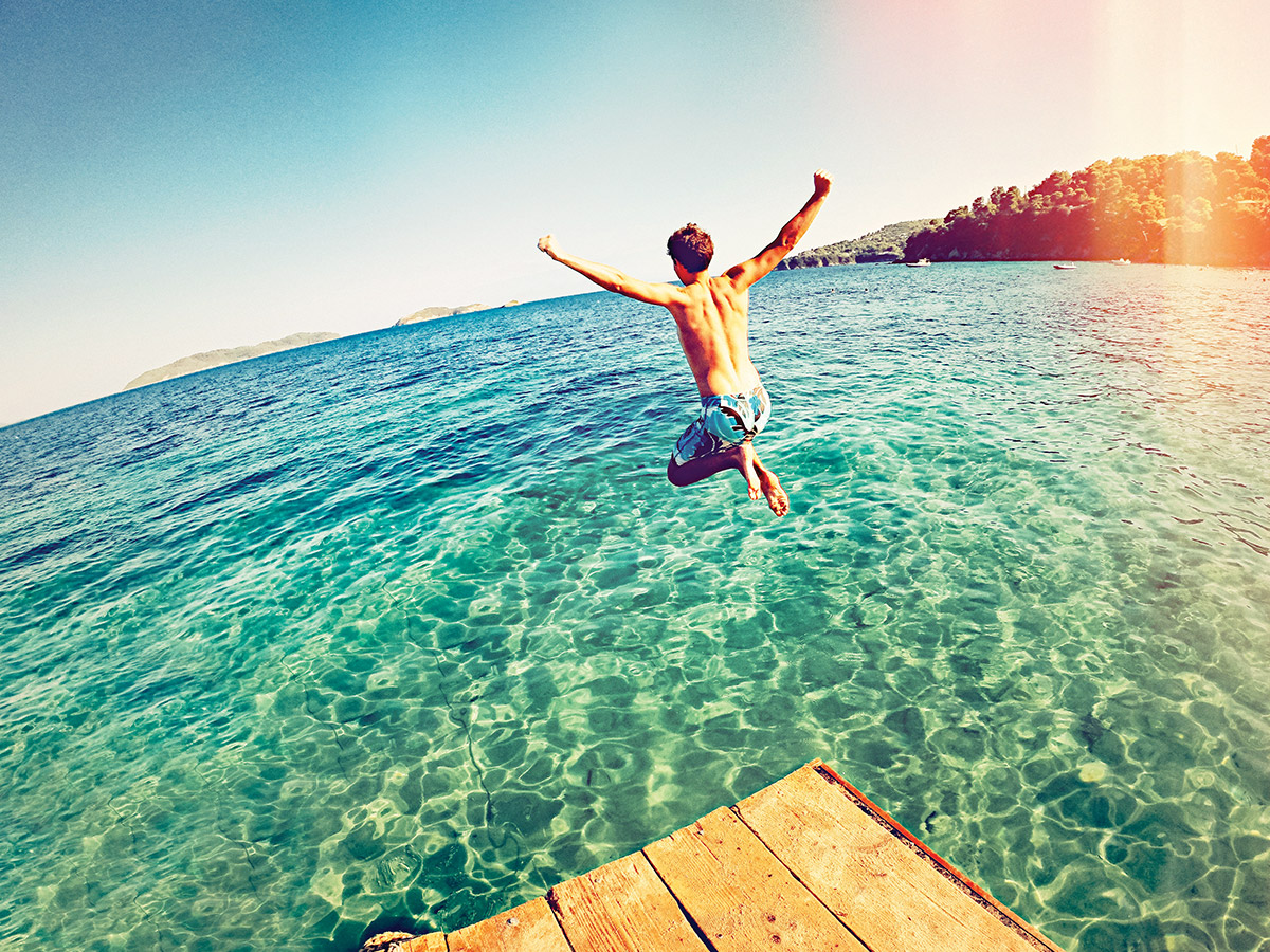 Young man jumps into a body of pristine water on a summer day