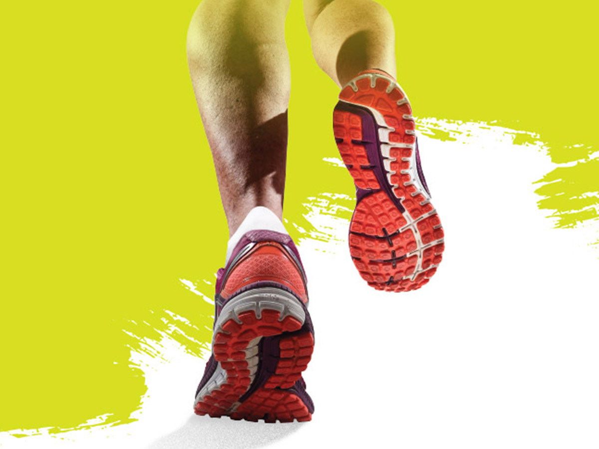 Crop of woman's legs in running shoes on a pain splattered lime-green background.