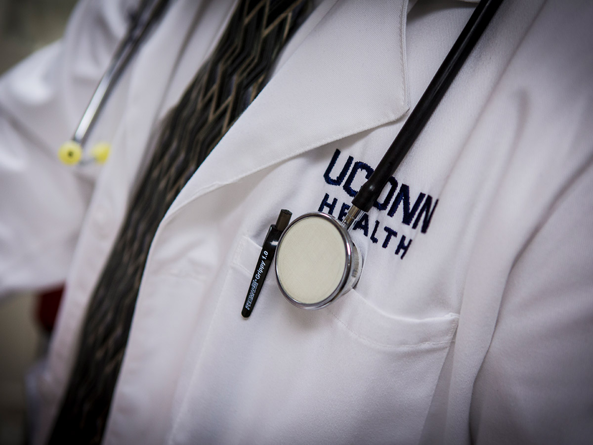 A close-up of UConn Health doctor wearing a lab coat with branding.
