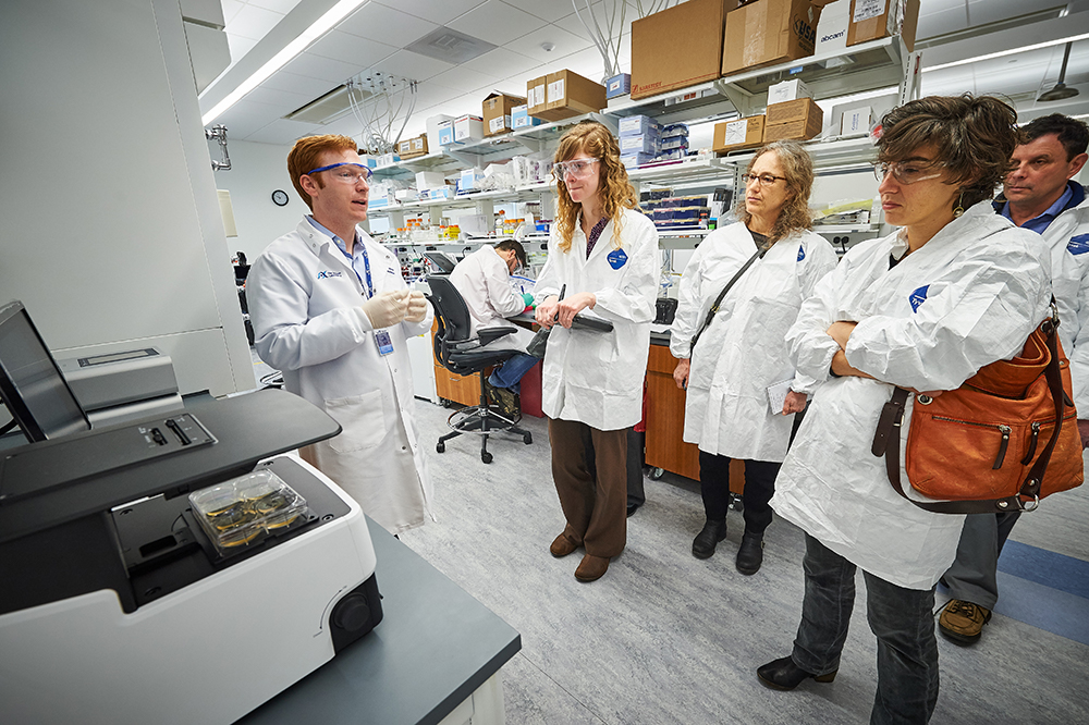 Dr. Travis Hinson speaks with others in his lab