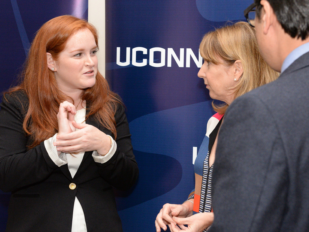 UConn fourth-year medical student Kaitlin Markoja talks with Donna McKay, executive director of Physicians for Human Rights (PHR), and Glenn Mitoma, director of UConn's Thomas J. Dodd Research Center.